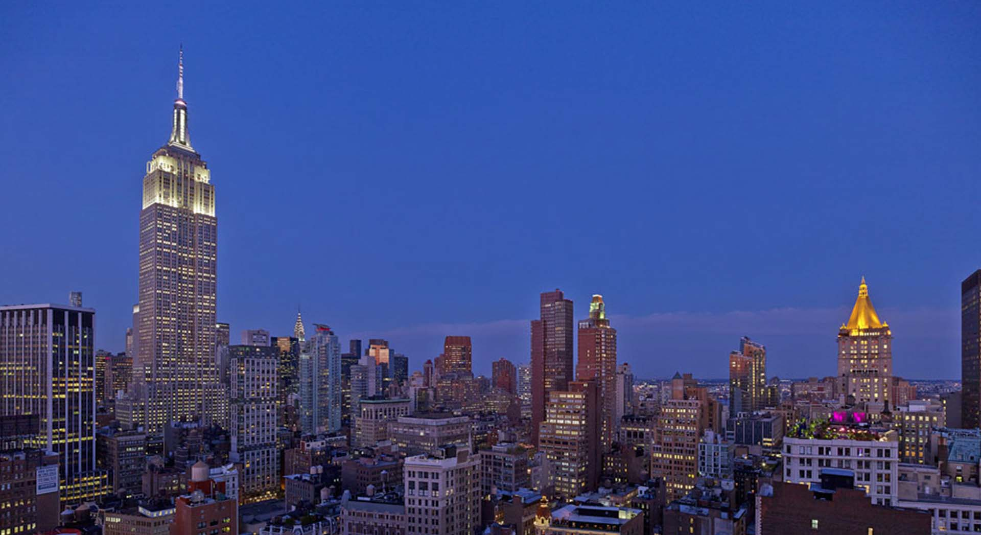 View of the manhattan skyline at dusk with the empire state building illuminated in white