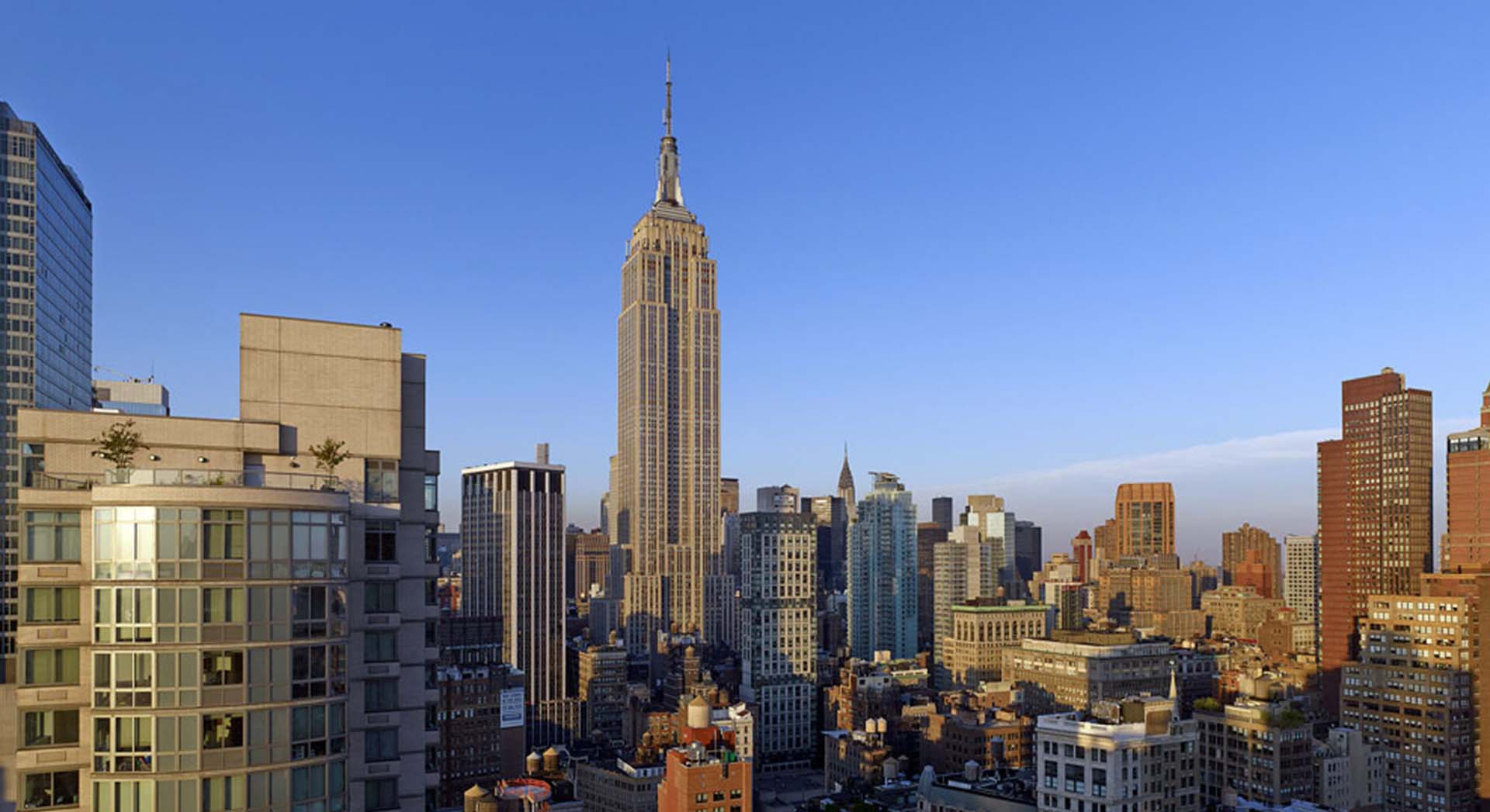 rooftop view of manhattan looking uptown during the day with clear skies and empire state building
