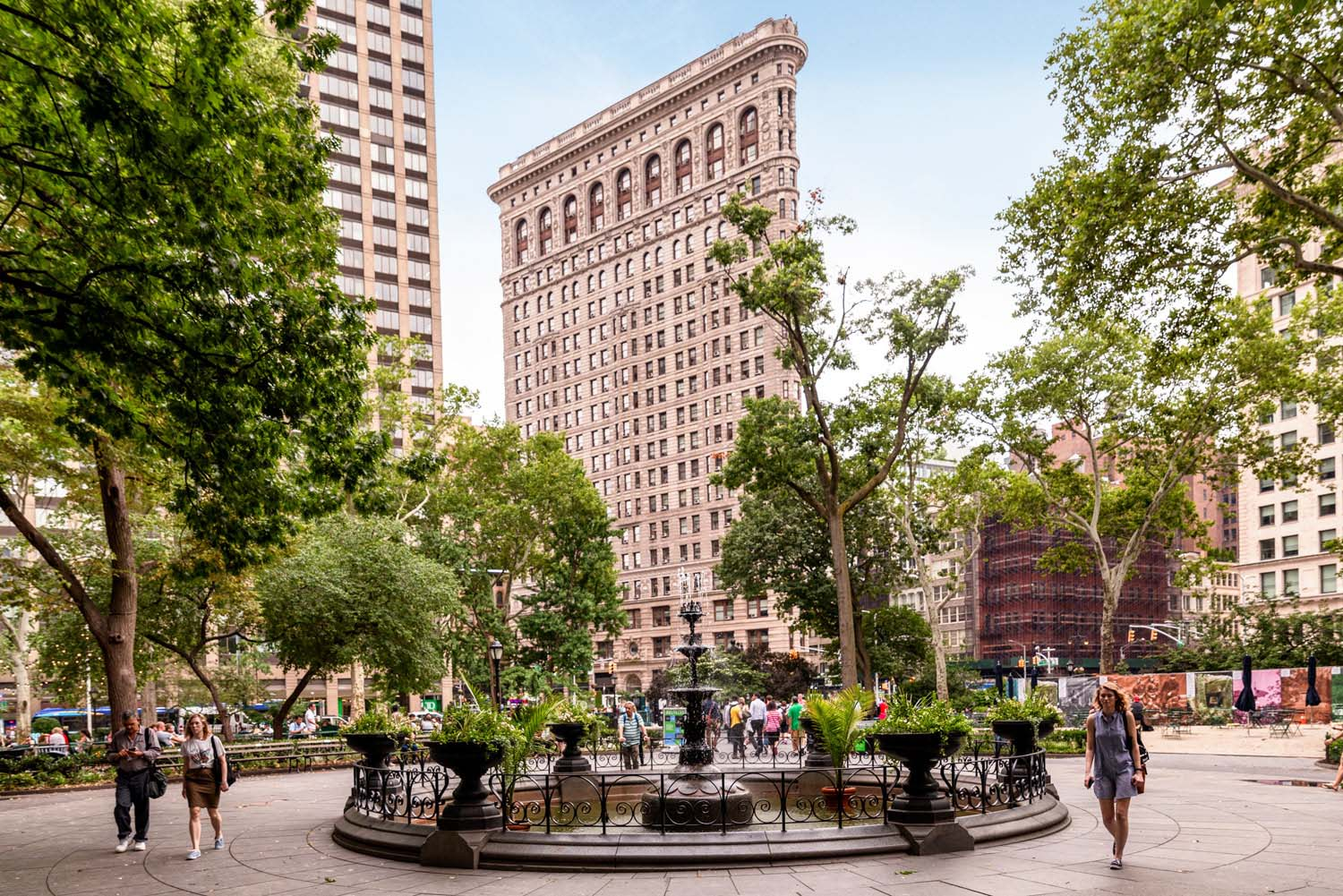 New York city park with fountain during the day with people walking and the flatiron building behind