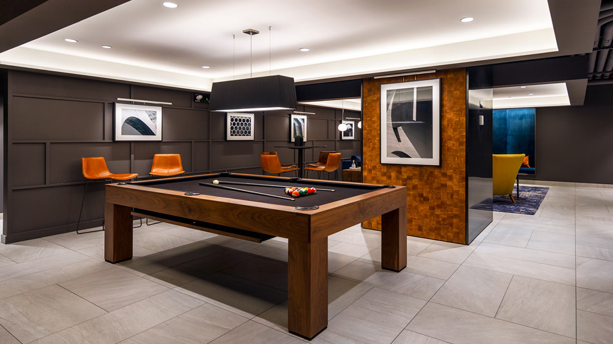 Game lounge with black felt pool table and marble floors, black walls, and art deco wood detailing