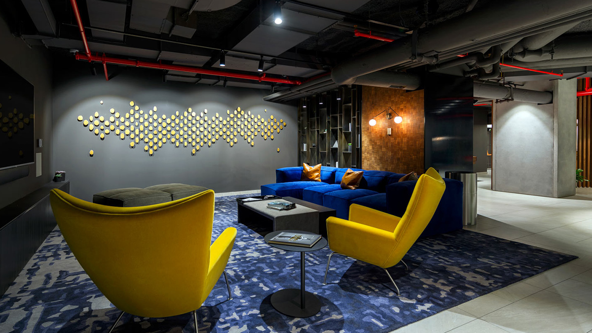 Lounge with modern art on wall, large yellow chairs and blue couch in velvet finish